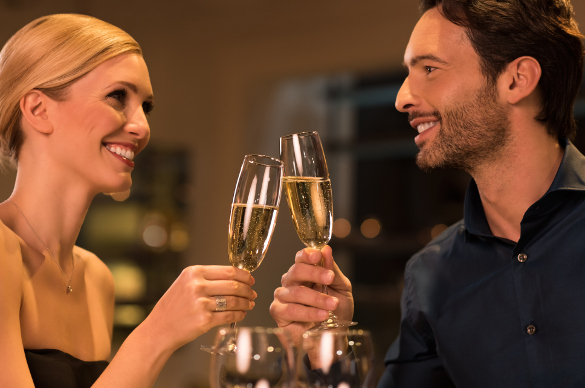Happy young couple celebrating their marriage anniversary in a luxury restaurant. Loving couple raising a toast with champagne and looking at each other. Beautiful couple enjoying their date in a restaurant.  (Happy young couple celebrating their marr